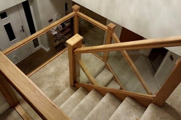 Wooden staircase for a grand hallway with glass panels for the balustrade