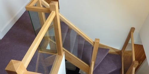 Oak stairs with glass panel balustrade and carpeted for comfort