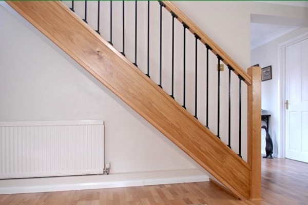 Oak and metal stairs. A straight staircase with a handrail featuring metal spindles