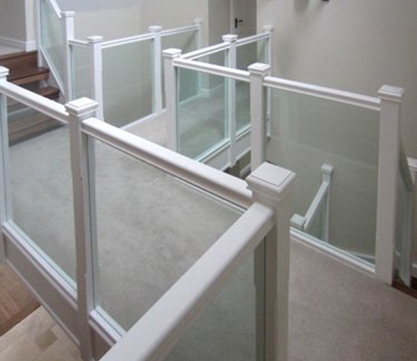 Landing with a glass balustrade with a white handrail